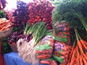 Bunch carrots, bagged carrots, green onions, red onions, gold beets, red beets at farmer's market